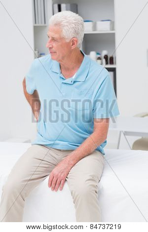 Senior man suffering from backache while sitting on bed in clinic