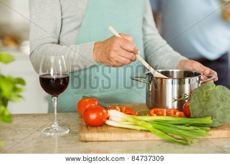 Mature couple making dinner together having red wine at home in the kitchen