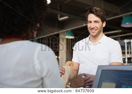 Customer paying her bread to waiter at the bakery