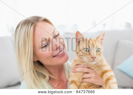 Beautiful young woman holding cat at home