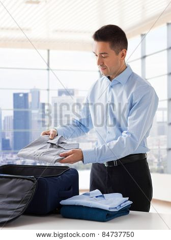 business, trip, luggage and people concept - happy businessman packing clothes into travel bag over home or hotel room background