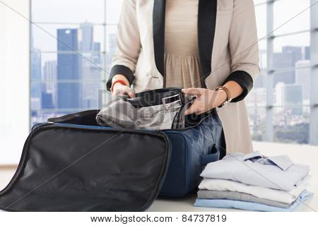 business, trip, luggage and people concept - close up of woman formal male clothes into travel bag at home or hotel
