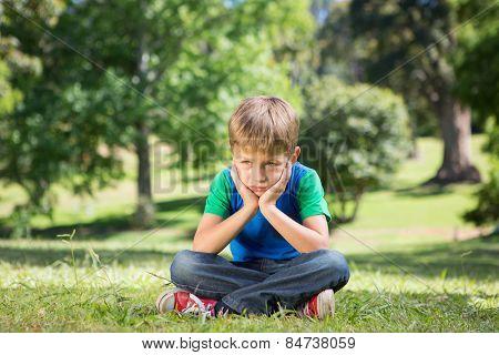 Little boy feeling sad in the park on a sunny day