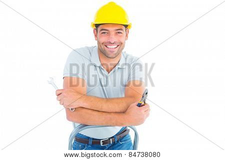 Portrait of repairman with hand tools on step ladder over white background