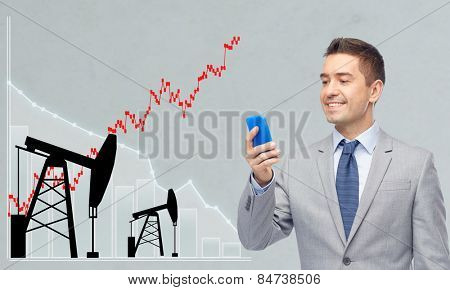 oil business, people, stock market, exchange rate and technology concept - happy businessman texting on smartphone over pump jacks and forex chart gray background