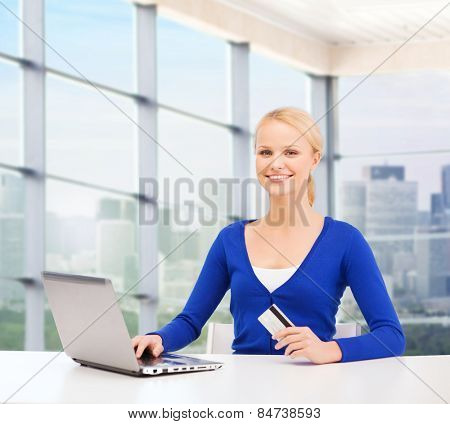 online shopping, banking, business and people concept - happy businesswoman with laptop and credit card over office window background