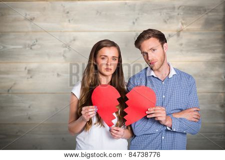 Couple holding broken heart against bleached wooden planks background