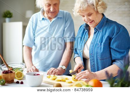 Senior woman cutting banana with her husband near by