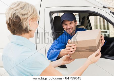 Delivery driver handing parcel to customer in his van outside the warehouse