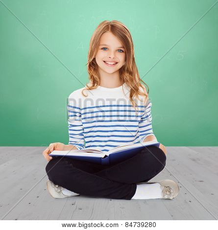 education, childhood, people and school concept - little student girl studying and reading book over green chalk board background