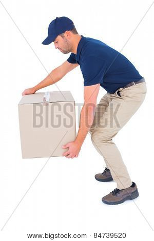 Full length side view of courier man picking up cardboard box on white background