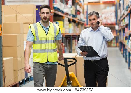 Worker walking with his manager over the phone in warehouse