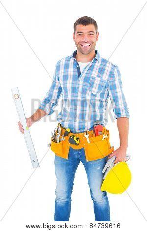 Portrait of smiling manual worker holding spirit level on white background