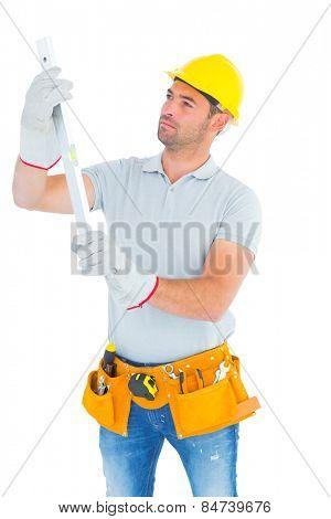 Handyman examining spirit level on white background