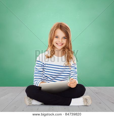 education, school, technology, childhood and people concept - happy little student girl with tablet pc over green chalk board background