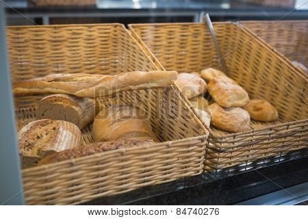 Baskets with breads freshly baked and tongs at the bakery