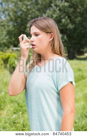Pretty blonde using an asthma inhaler on a sunny day