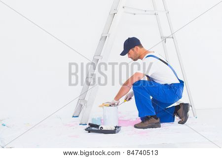Full length side view of handyman in overalls opening paint can at home