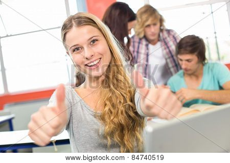 Portrait of happy female student gesturing thumbs up in classroom