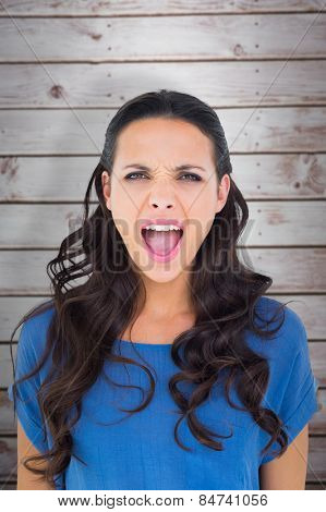 Angry brunette shouting at camera against wooden planks