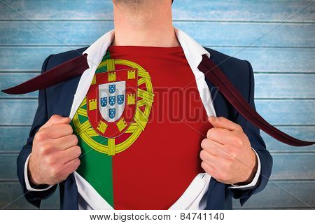 Businessman opening shirt to reveal portugal flag against wooden planks