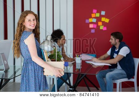 Portrait of beautiful casual businesswoman carrying her belongings in box