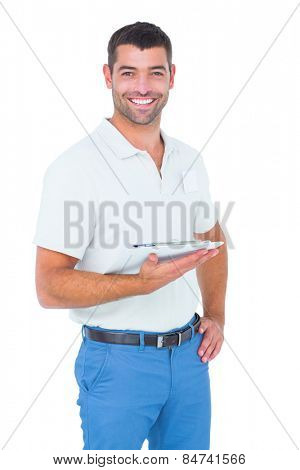 Portrait of smiling handyman with clipboard on white background