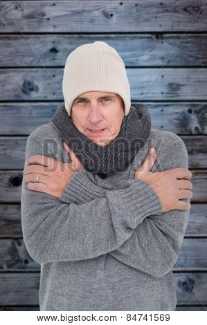 Casual man shivering in warm clothing against wooden background in blue