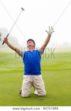 Kneeling golfer cheering on putting green on a foggy day at the golf course