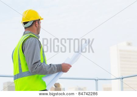 Side view of male architect in protective workwear holding blueprints outdoors