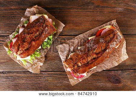 Fresh and tasty sandwiches with ham and vegetables on wooden background