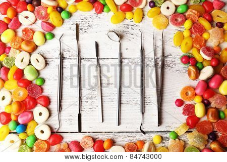 Dentist tools with sweets on wooden background