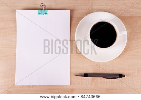 Cup of coffee on saucer with sheet of paper and pen on wooden table background