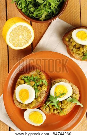 Sandwiches with green peas paste and boiled egg on plate with napkin on wooden planks background