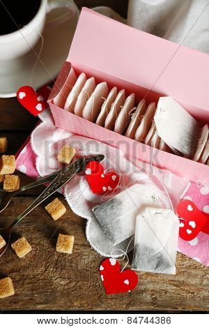 Heart shaped teabag tags and box on wooden background