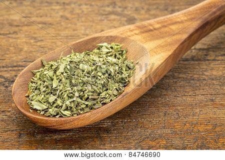 organic dried oregano leaf on a wooden spoon against a grunge wood background