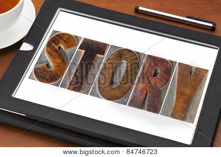 story word in vintage letterpress wood type printing blocks on a digital tablet with a cup of tea