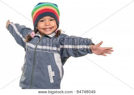 Happy mixed race little girl wearing a colorful beanie hat offering a hug with wide open arms isolated on white