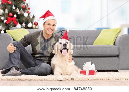Man and a dog with Santa hats sitting by a sofa at home