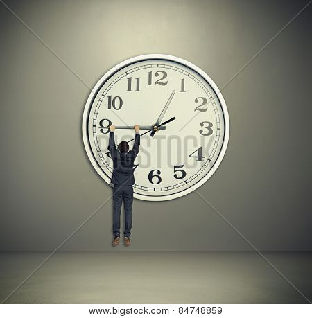 businessman hanging on big clock hand. big clock on grey wall