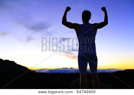 Strength - strong success fitness man flexing muscles showing power pose outside in silhouette at night. Muscular fit male fitness man celebrating success macho style.