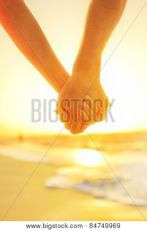 Couple in love holding hands - happy relationship. Closeup of male and female arms together at beach sunset during holidays tropical vacations.