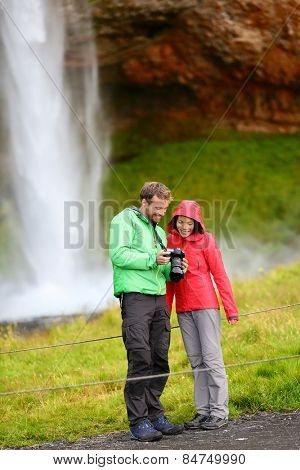 Tourists with SLR camera by waterfall on Iceland. Romantic couple visiting famous tourist attractions and landmarks in Icelandic nature landscape by Seljalandsfoss waterfall on Ring Road.