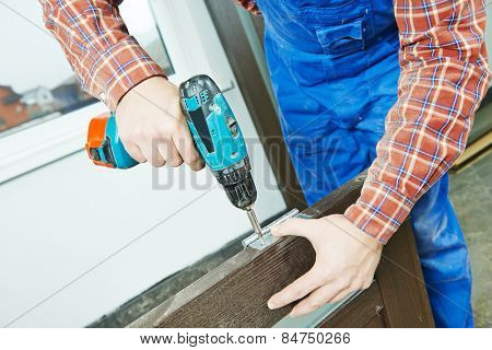 carpenter at interior wood door lock installation working with drill