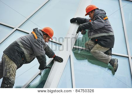 two industrial builder workers at outdoors window installation