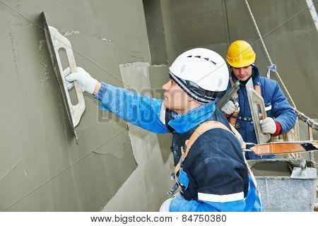 builders at facade plastering work during industrial building with putty knife float