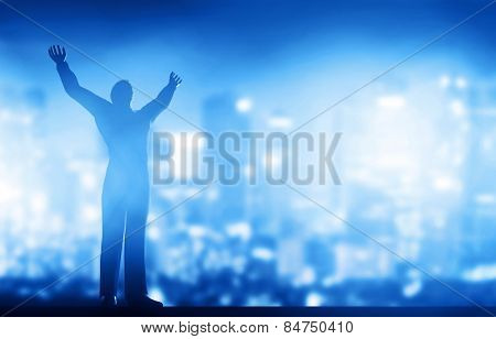 Successful businessman with hands up against city downtown at night background. Conceptual