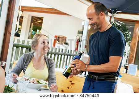 waiter with balsamic sauce serving female client in small italian restaurant