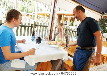 waiter with pizza on plate serving in small italian restaurant