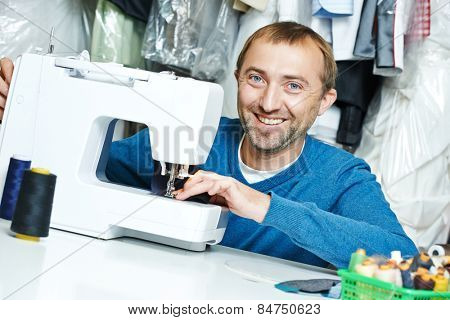 male tailor working with sewing machine and cloth in workshop
